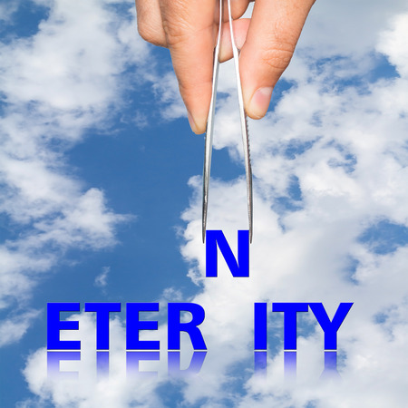 potentiality: hand with the forceps and the word eternity on the background. Stock Photo