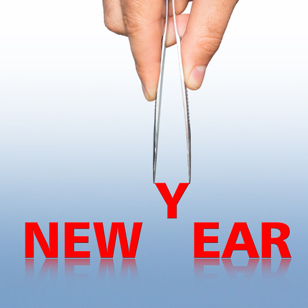 pinzas: Word new year and hand with tweezers on  background