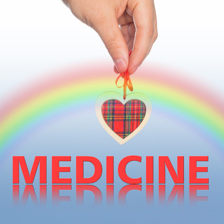 word medicine: hand with  heart and  word medicine on the background.