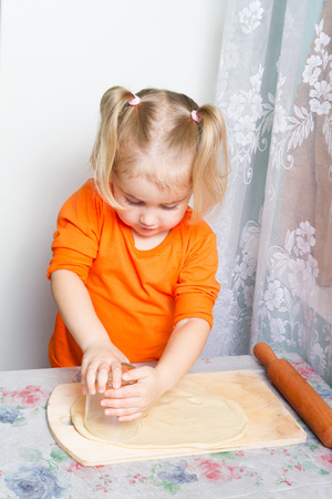 little dough: Little girl making dough in the kitchen with a rolling pin.