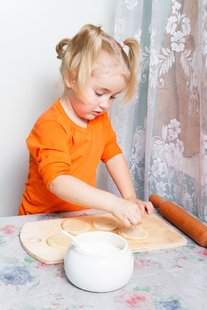 cute blonde: Little girl making dough in the kitchen with a rolling pin.