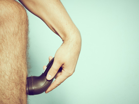 piernas hombre: Close up of young Caucasian man shaving hair from legs