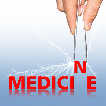 word medicine: hand with  forceps and  word medicine on the background. Stock Photo