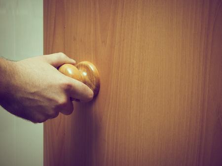 room door: Caucasian Man opens wood the door.indoor