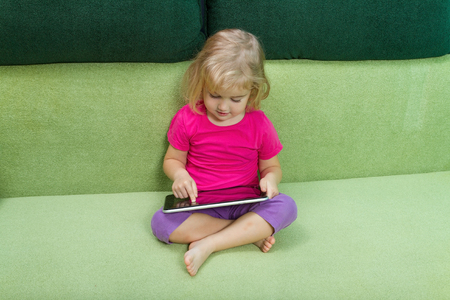 Cute little girl using tablet computer sitting on a green couch.