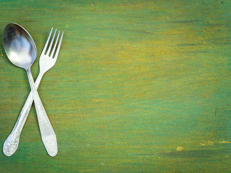 grunge flatware: Fork and spoon on old wooden table. Vintage texture, background. Menu. Stock Photo