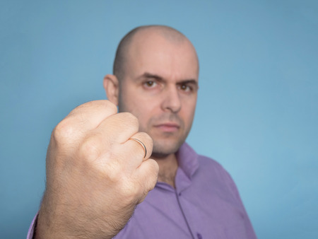 gestos de la cara: Angry Caucasian bald man with clenched fist