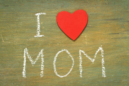 Text i love mom written with chalk in old board wooden.