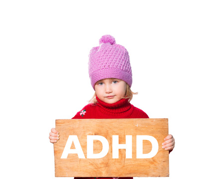 hyperactivity: Little girl holding Board with inscription ADHD. Isolated on white background Stock Photo