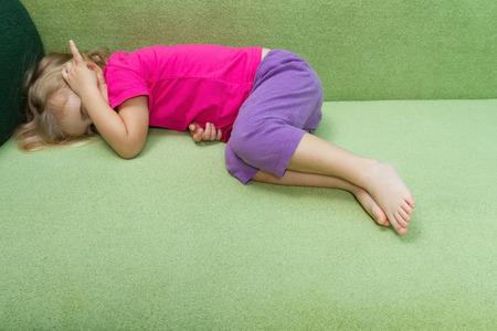 petite fille triste: Sad petite fille couchée sur le sofa.Covered sa tête avec sa main. Problèmes de famille. Banque d'images