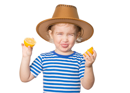 Little Funny girl in striped shirt and hat keeps lemons. Isolated on white background Banque d'images