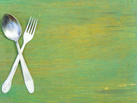 Fork and spoon on old wooden table. Vintage texture, background. Menu. Stockfoto