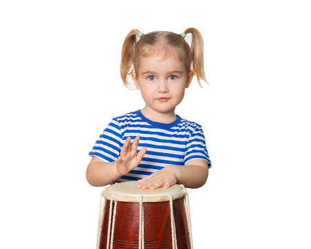 Little Funny girl in striped shirt play drum. Isolated on white background Stockfoto