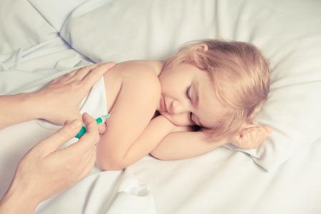 inyeccion intramuscular: Mujer que hace la inyecci�n con una jeringa en la mano del ni�o