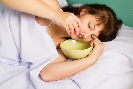 lavage: Woman lying on the bed, washes the nose. Stock Photo