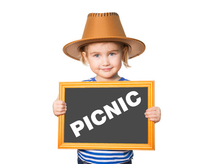 Little Funny girl in striped shirt with blackboard. Text PICNIC. Isolated on white background. Stock Photo