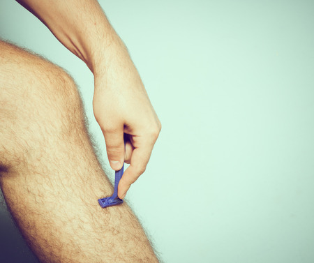 depilate: Close up of young Caucasian man shaving hair from legs