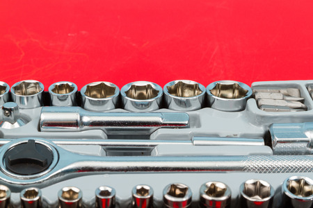 ratchet: Ratchet and a set of interchangeable heads for chrome socket wrench. Isolated on red table. Stock Photo