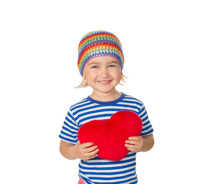Little girl holding a red heart toy. Isolated on a white background.