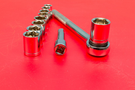 socket wrench: Ratchet and a set of interchangeable heads for chrome socket wrench. Isolated on red table. Stock Photo