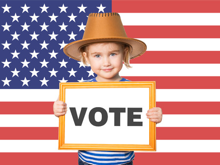 politics: Little Funny girl in striped shirt with blackboard. Text VOTE. On background of American flag. Stock Photo