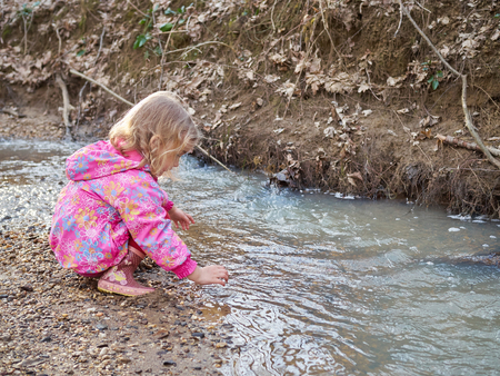 cute girl: Cute little girl sitting on the Bank of the river in the forest. Stock Photo