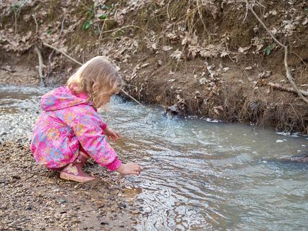 bebes ni�as: Ni�a linda que se sienta en el banco del r�o en el bosque.