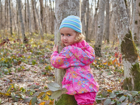 jungle girl: Cute little girl hugging a tree trunk in the spring forest. Protection of nature.