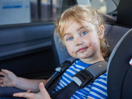 dirty blond: Little dirty girl , baby in a safety car seat. Safety and security Stock Photo