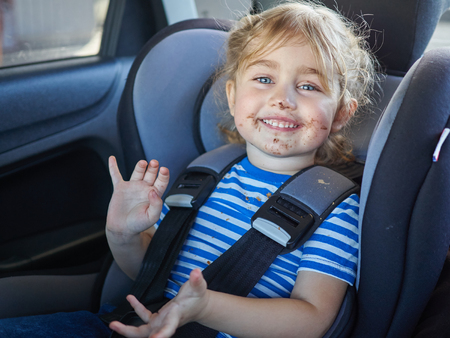 dirty car: Little dirty girl , baby in a safety car seat. Safety and security Stock Photo