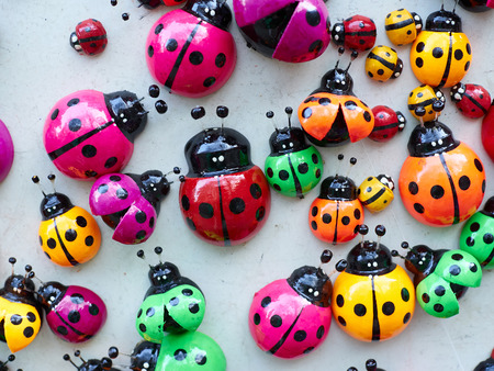 coccinella: Lots of colorful wooden ladybugs. Toys, magnets. Stock Photo