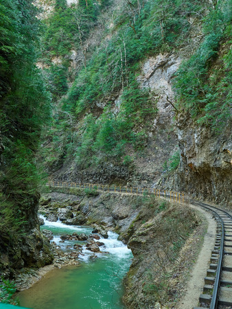 narrow gauge railroad: Mountain Stream and railroad in Springtime. Cascade river over mossy rocks.