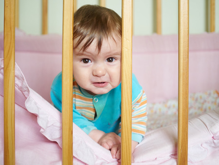 rueful: Little baby in a cot. Portrait child baby close up.