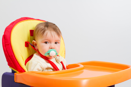 highchair: Baby with a pacifier at home sitting in highchair