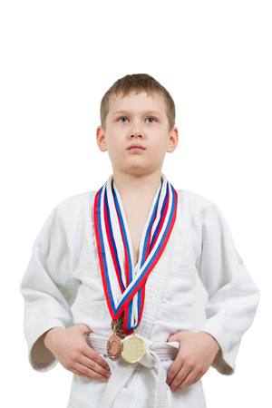 karate boy: Karate boy in white kimono with medals fighting isolated on white background Stock Photo