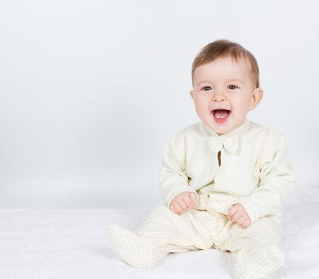 lachendes gesicht: Little Baby lustiger Junge in Anzug sitzt. Auf Weiß.