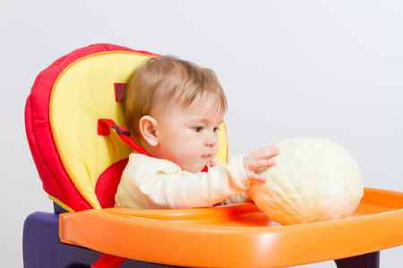 highchair: baby sits in the highchair with cabbage. Stock Photo