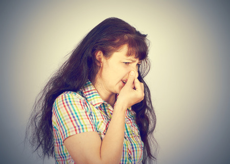 young woman holding her nose because of bad smell on a gray background
