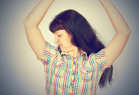 intolerable: young woman, smelling, sniffing her armpit, something stinks, very bad foul odor isolated grey background. Stock Photo