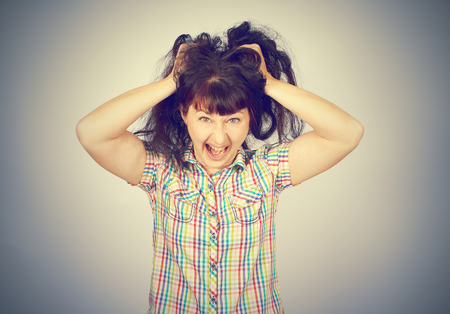 Angry crazy caucasian young girl grabs hair on gray background
