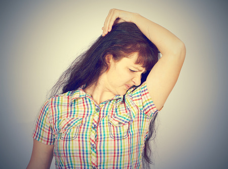 stinks: young woman, smelling, sniffing her armpit, something stinks, very bad foul odor isolated grey background. Stock Photo