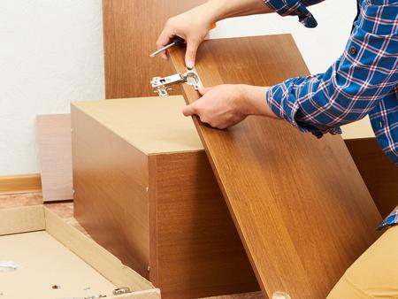 Man in shirt assemble furniture. Domestic work. Craftsman. Carpenter. Standard-Bild