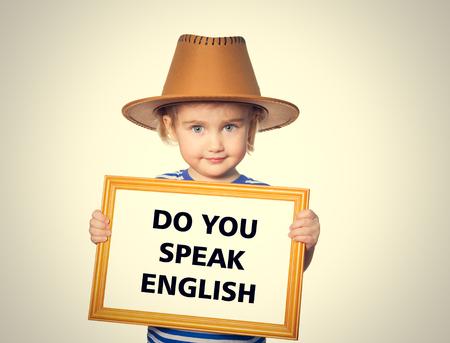 idiomas: Niña divertida en camisa rayada con la pizarra. El texto habla usted Inglés.