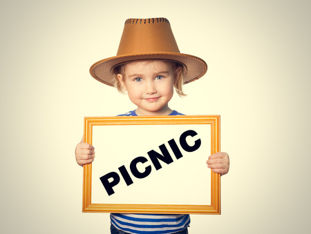 picknick: Little Funny girl in striped shirt with blackboard. Text PICNIC.