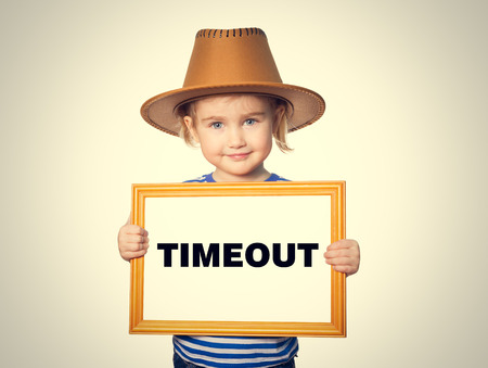 timeout: Little Funny girl in striped shirt with blackboard. Text TIMEOUT. Stock Photo