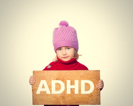 rueful: Little girl holding Board with inscription ADHD. Stock Photo