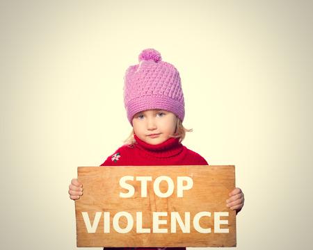 Niña que sostiene la Junta con la violencia parada texto. Foto de archivo