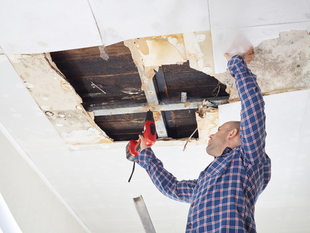 Man repairing collapsed ceiling. Ceiling panels damaged huge hole in roof from rainwater leakage