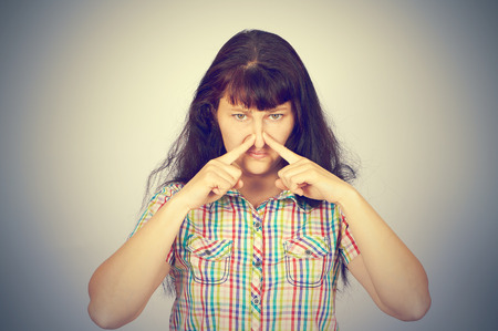 unbearable: young woman holding her nose because of bad smell on a gray background