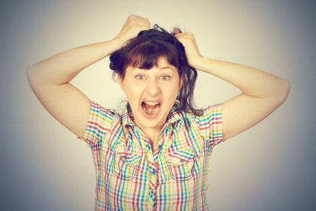 bad temper: Angry crazy caucasian young girl grabs hair on gray background